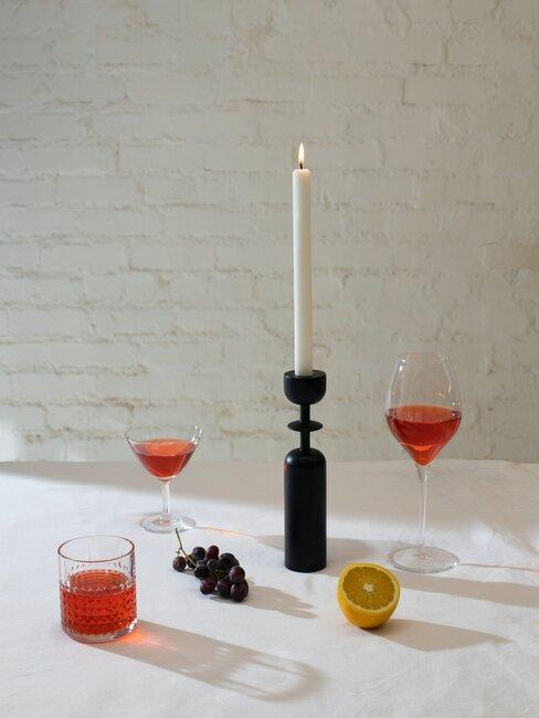 Dwa kieliszki różowego wina i świeczka na stole
