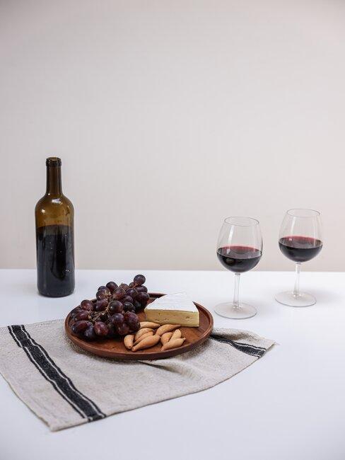 Butelka czerwonego wina, dwa kieliszki, talerz z winogronami, serem i migdałami