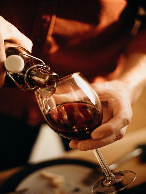 Ręka nalewająca wino z butelki do kieliszka