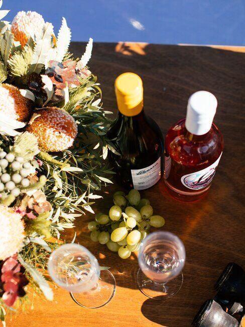 Dwie butelki wina stojące na stole obok kieliszków