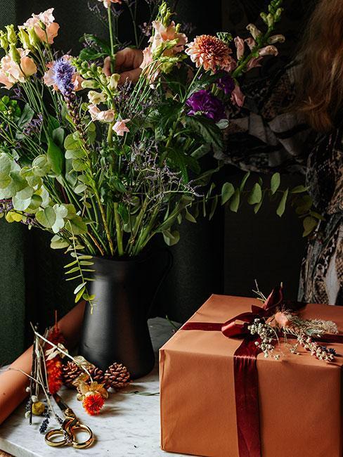 Prezent opakowany w pomarańczowy papier obok bukietu świeżych polnych kwiatów