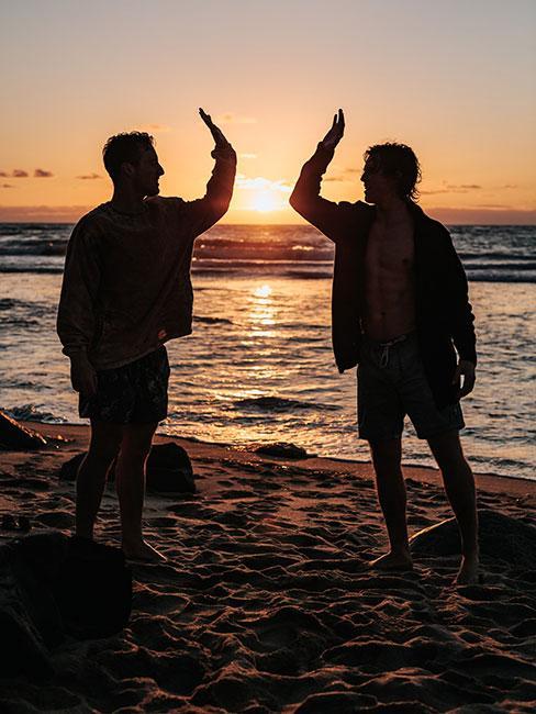dwóch mężczyzn na plaży na tle zachodu słońca