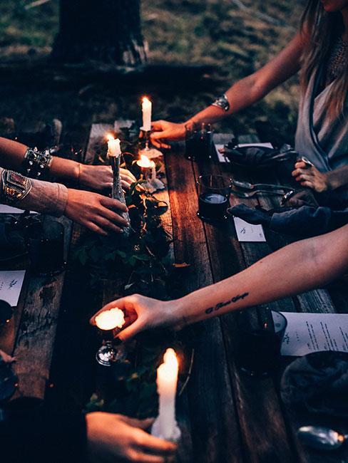 Kobiece dłonie ustawiające świeczki na drewnianym stole na zewnątrz
