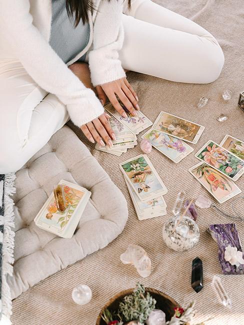 Młoda kobieta wróżąca z kart na dywanie