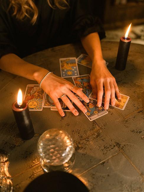 Zbliżenie na dłonie na stole oświetlone świeczką układające tarota