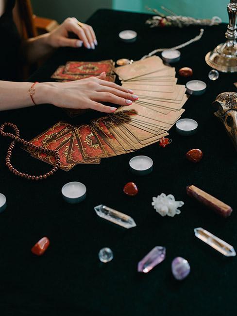 Karty tarota rozłożone na czarnym obrusie z kamieniami szlachetnymi