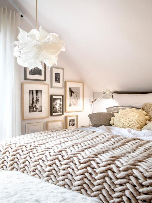 Sypialnia na poddaszu w stylu boho z beżową wełnianą narzutą i galerią grafik i zdjęć na ścianie