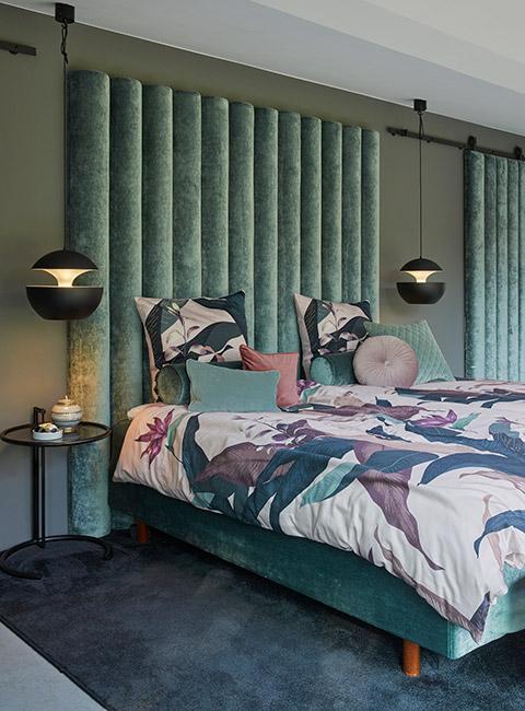 Sypialnia w stylu art deco z zielonym welurowym zagłówkiem i pościelą w tropikalny deseń