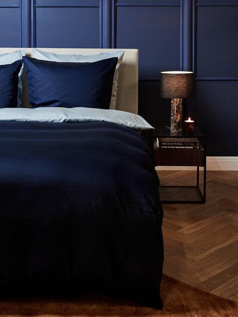 Sypialnia w kolorze granatu, drewniana podłoga i stolik przy łóżku
