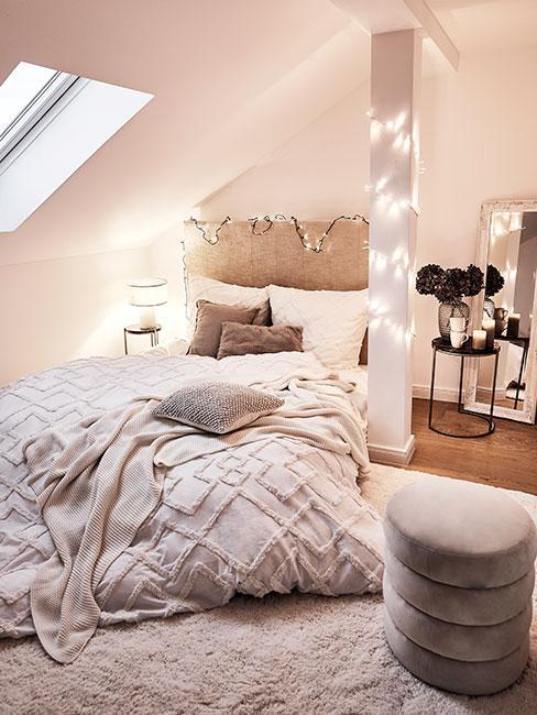 Sypialnia na poddaszu oświetlona giarlandami w jasnych kolorach
