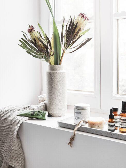 Kwiaty stojące na oknie w szarej łazience, obok kosmetyki