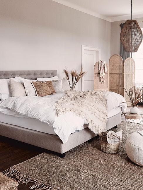 Sypialnia w beżowych odcieniach w stylu boho z parawanem i dekoracjami z susonych traw