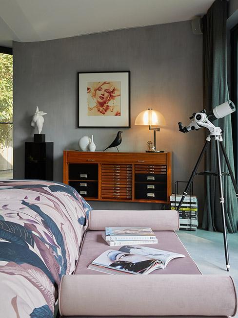 Sypialnia marzeń w stylu mid century modern z drewnianą komodą retro na tle szarej ściany i różowym szezlongiem z aksamitu