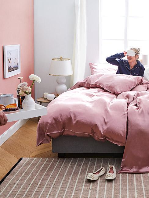 Kobieta w łóżku z różową pościelą zdejmująca maskę na oczy patrząca w kierunku tacy ze śniadaniem wnoszonej do sypialni