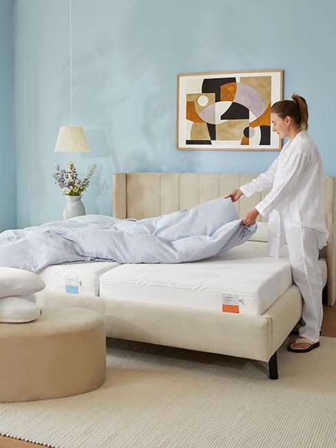 Kobieta w piżamie ścieląca łóko w jasnej sypialni