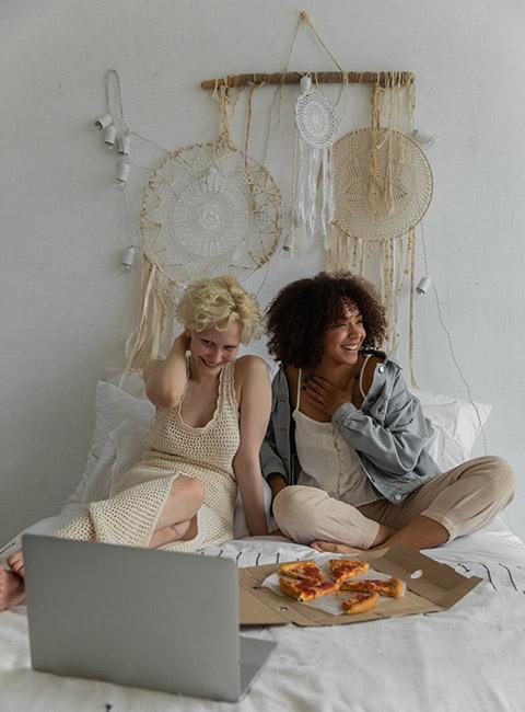 Dwie kobiety siedzące na łóżku z koronkowymi łapaczami snu na ścianie za łóżkiem