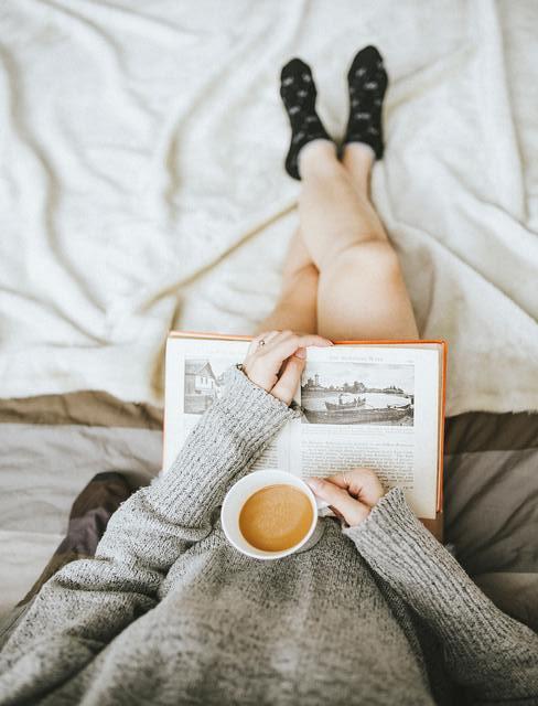 jak się rozbudzić: Osoba w szarym swetrze siedząca na łóżku trzymająca na kolanach książkę, a w ręce kubek z kawą