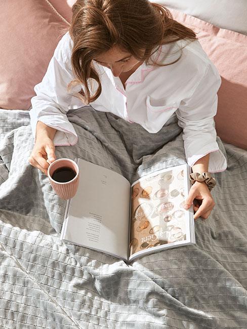 Kobieta ubrana w białą koszulę siedząca w łózku z kubkiem kawy i książką