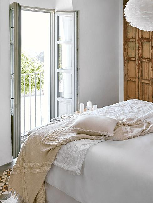Sypialnia z dużym łóżkiem z białą pościelą i otwartymi drzwiami na balkon