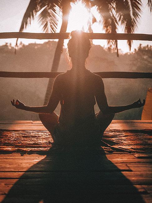 jak się rozbudzić: Osoba medytująca w blasku zachodzącego słońca