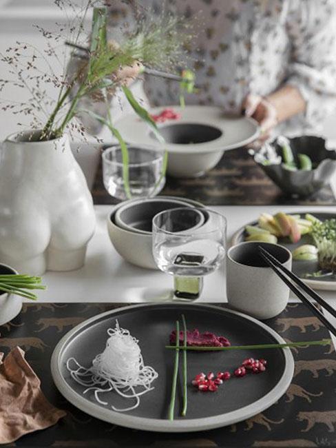 Lekkie śniadanie składające się z warzyw i makaronu ryżowego, podane na ciemnoszarych talerzach
