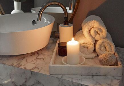 jak się rozbudzić: Kącik w łazience z białą umywalką, marmurowym blatem i tacą na której leży świeczka i rećzniki