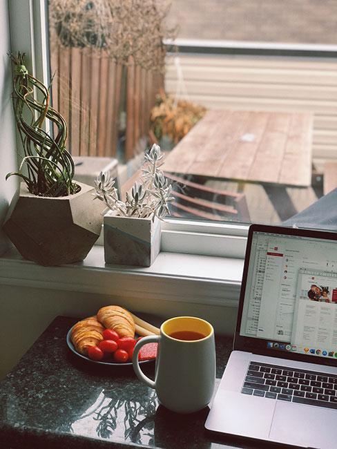 jak się rozbudzić: Taca ze śniadaniem, obok laptop a w tle okno z którego widać balkon na którym stoi stolik
