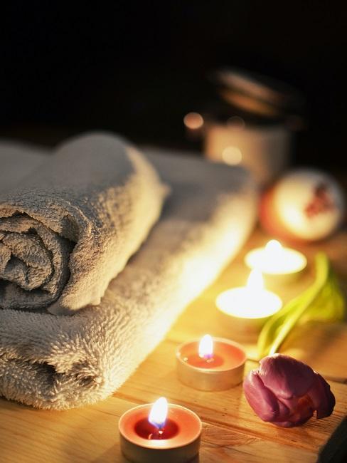 Świece na drewnianym stole z ręcznikami