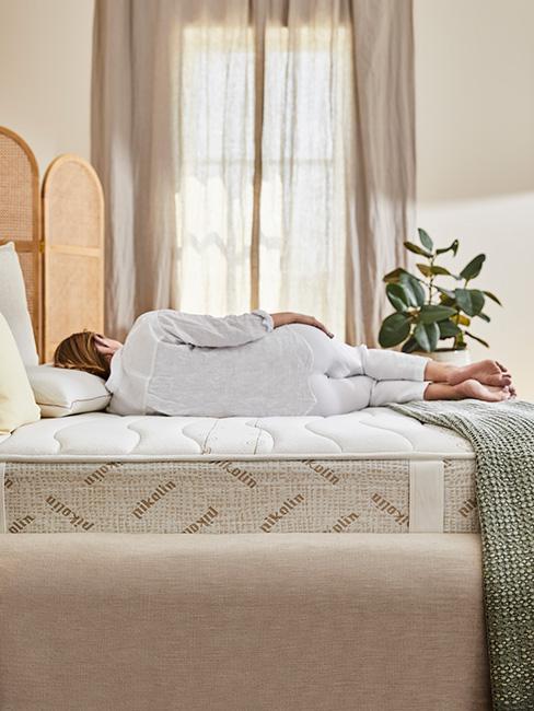kobieta w białek piżamie na białym materacu w jasnej sypialni