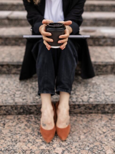 Kobieta w czarnym garniturze i kubkiem kawy siedząca na schodach