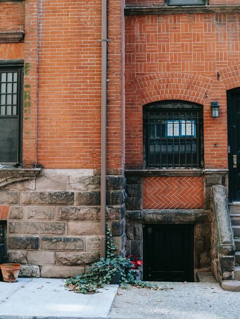 Dom z cegły z ozdobnym kamiennym dołem do którego dopasowane są schody