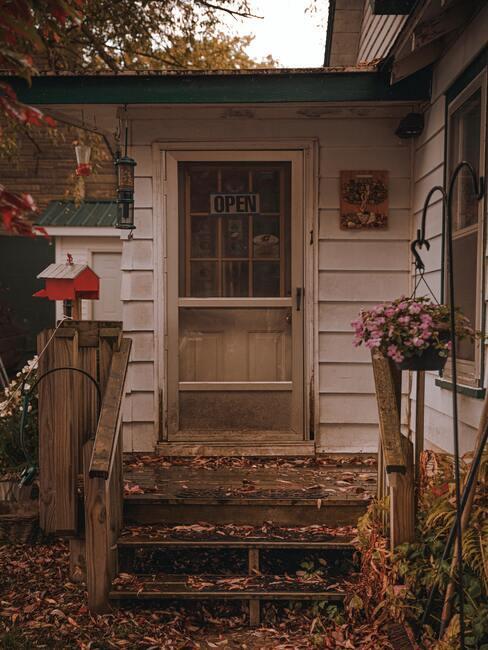 Drewniane schody wraz z drewnianą barierką prowadzące do domu