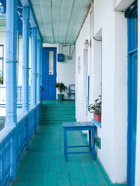 Wejście do domu z podłogą i schodami w kolorze turkusowym oraz barierką pomalowana na kolor niebieski