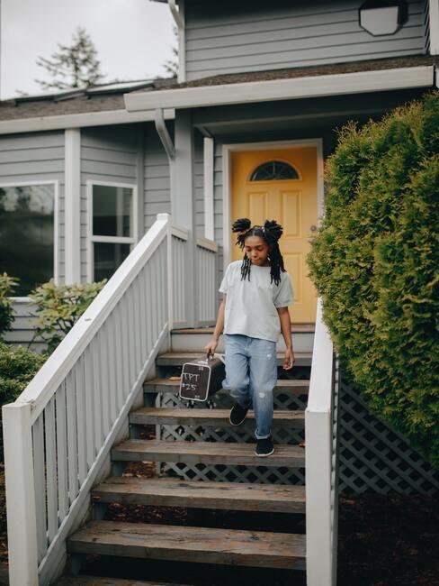 dziewczynka schodząca z drewnianych schodów przy których jest białą drewniana barierka