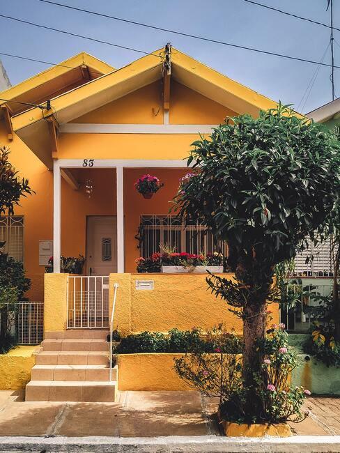 Żółty dom z żółtymi schodami i gankiem w takim samym kolorze