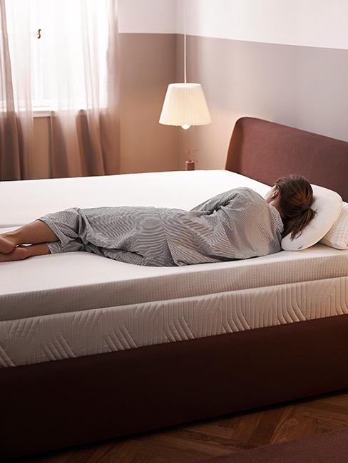 Kobieta leżąca na boku na brązowym łóżkiem w przytulnej sypialni