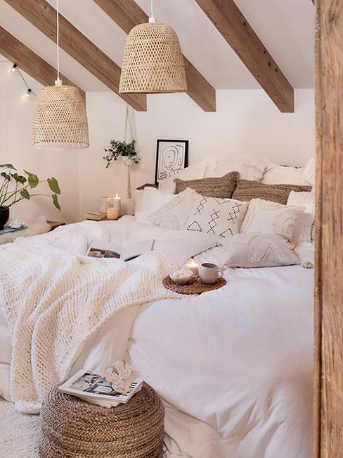 Rustykalna sypialnia na poddaszu z belkami z wiszącymi lampami z rafii