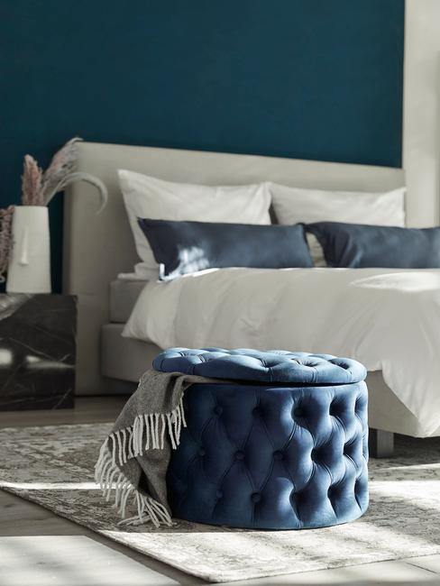 Wnętrze sypialni z ciemnoniebieską ścianą i pufem