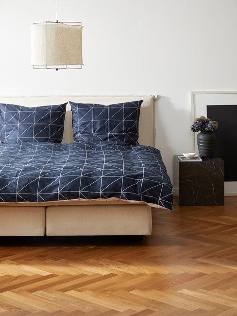 Przestronna sypialnia z jasnymi ścianami i ciemną pościelą
