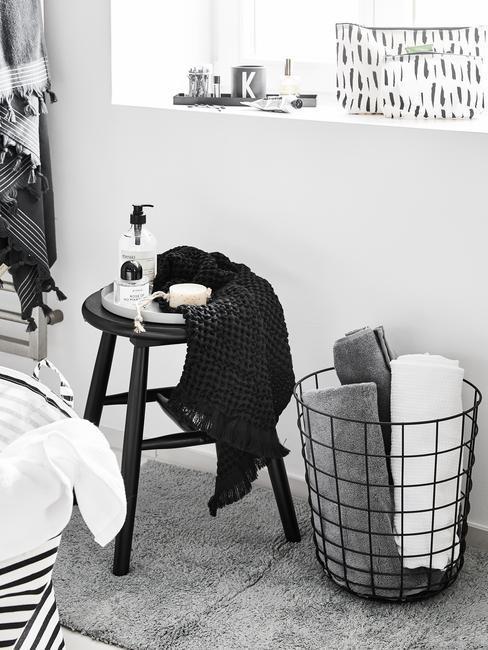 Czarny taboret w łazience, obok metalowy kosz na ręczniki