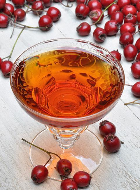 Nalewka z głogu oraz porozrzucane owoce na stole