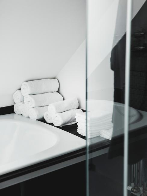 Białe ręczniki zwinięte w rolki na brzegu umywalki