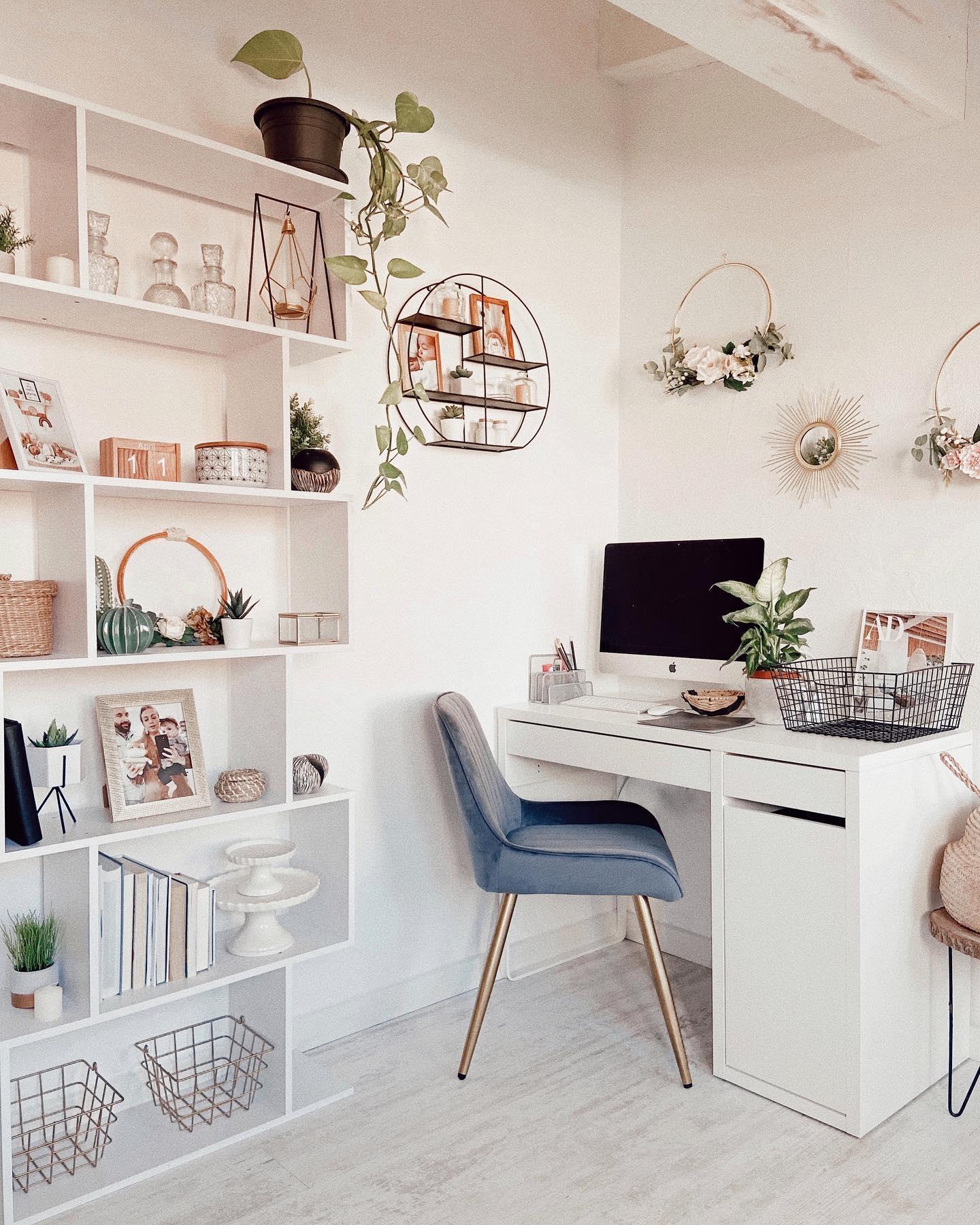 Biurko w kąciku w sypialni obok białego regału z dekoracjami