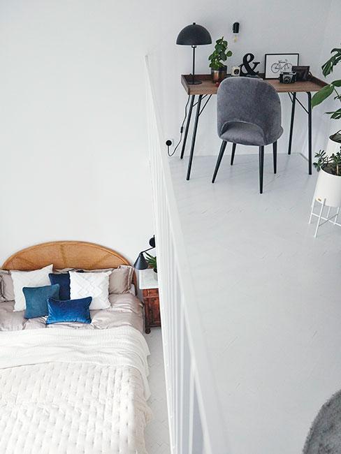 Sypialnia z półpiętrem, na którym jest biurko z szarym krzesłem