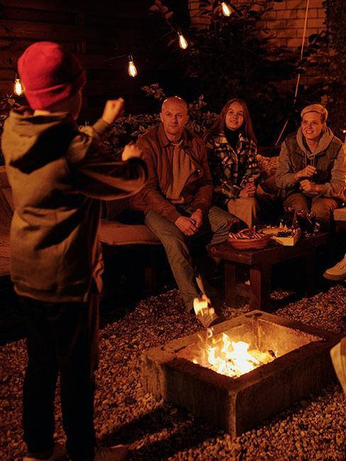grupa ludzi gra zagadki pantomimiczne na dworze przy ognisku