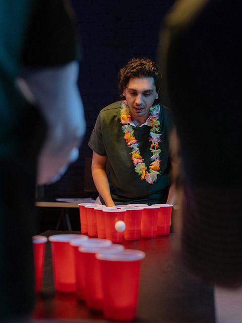 Młody mężczyzna gra w beer pong z czerwonymi kubeczkami na stole