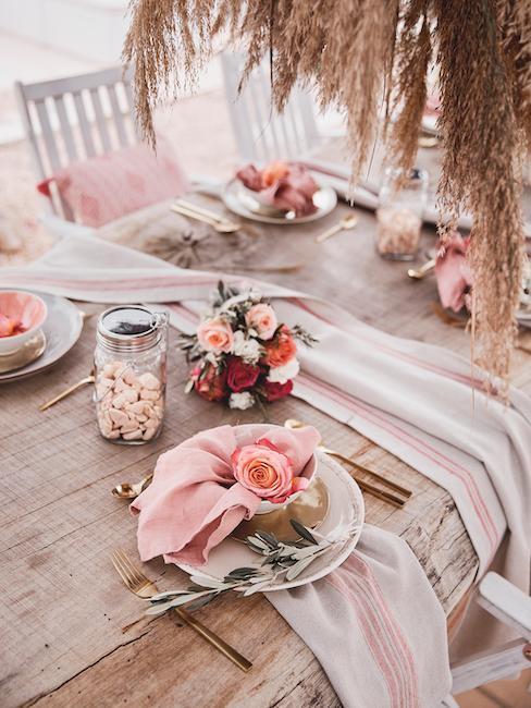 Drewniany stół na plaży udkorowany różami i trawami w stylu boho