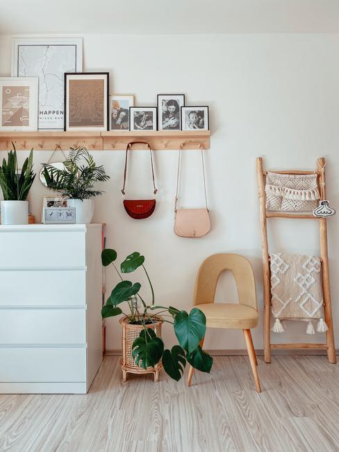 Štylizácia kútika v domácnosti s bielou komodou, stoličkou s čalúnením a bytovými dekoráciami a textilom