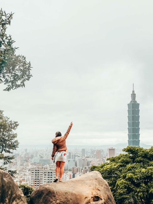Veronika z blogu She makes me travel stojaca na skale a pozorujúca výhľad na mesto