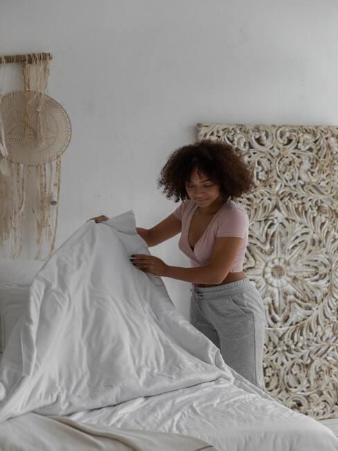 žena ustlajúca posteľ